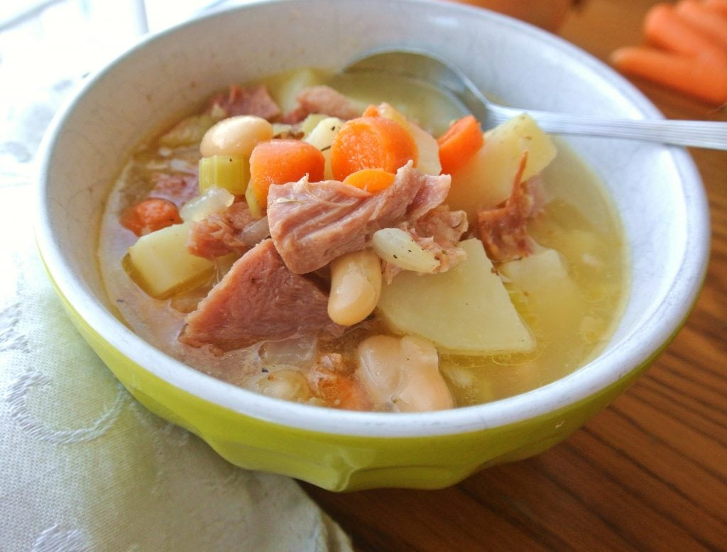 This One Pot Ham, Potato and Bean Soup is made by stewing a ham bone in chicken stock which renders a flavorful broth and adding vegetables and seasonings.