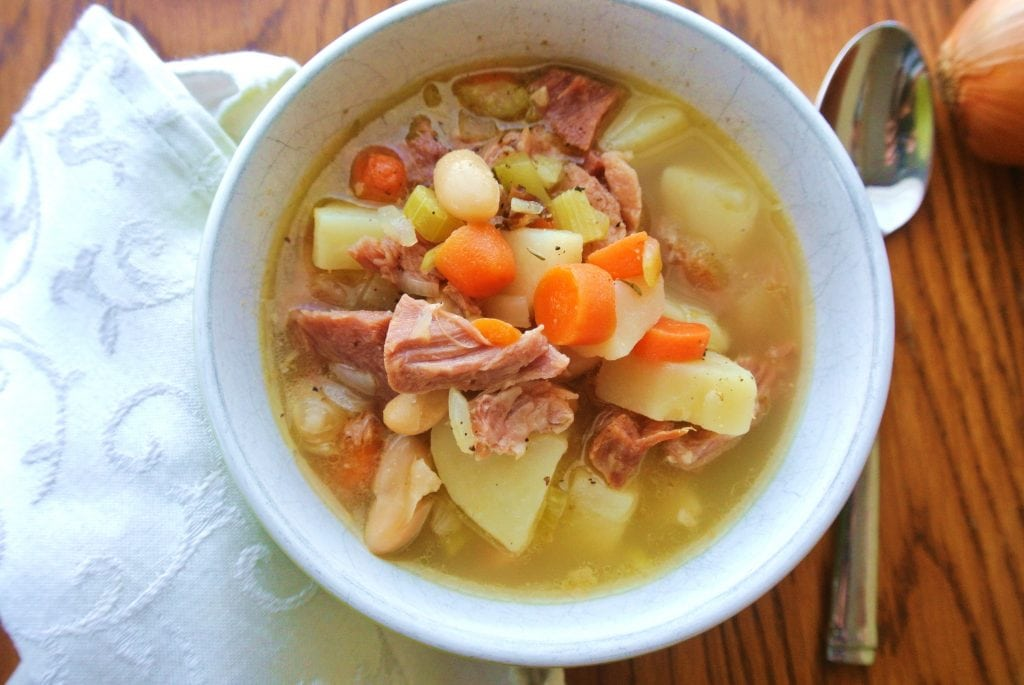 This One Pot Ham, Potato and Bean Soup is made by stewing a ham bone in chicken stock which renders a flavorful broth and adding vegetables and seasonings. Comfort food!