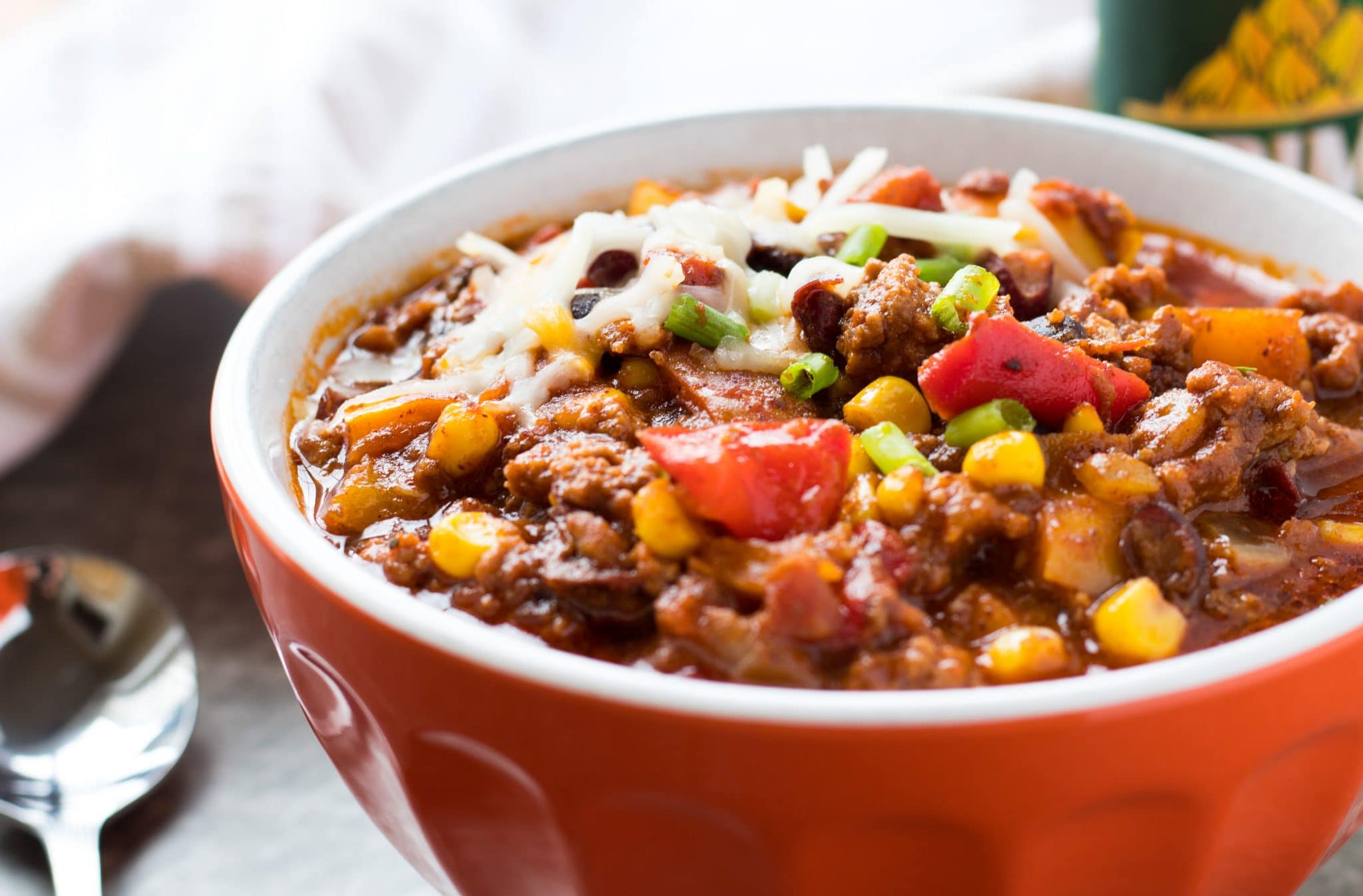 This Loaded Slow Cooker Chili is loaded with ground beef, beans, corn, rainbow bell peppers and spices. Sweetened with honey. Tasty game day food!